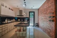 Rustic look red brick wall the highlight of the kitchen ...