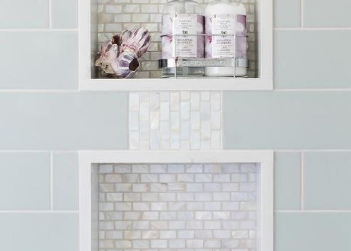 Blue subway shower tiles frame two white glass mini brick tiled niches connected by also