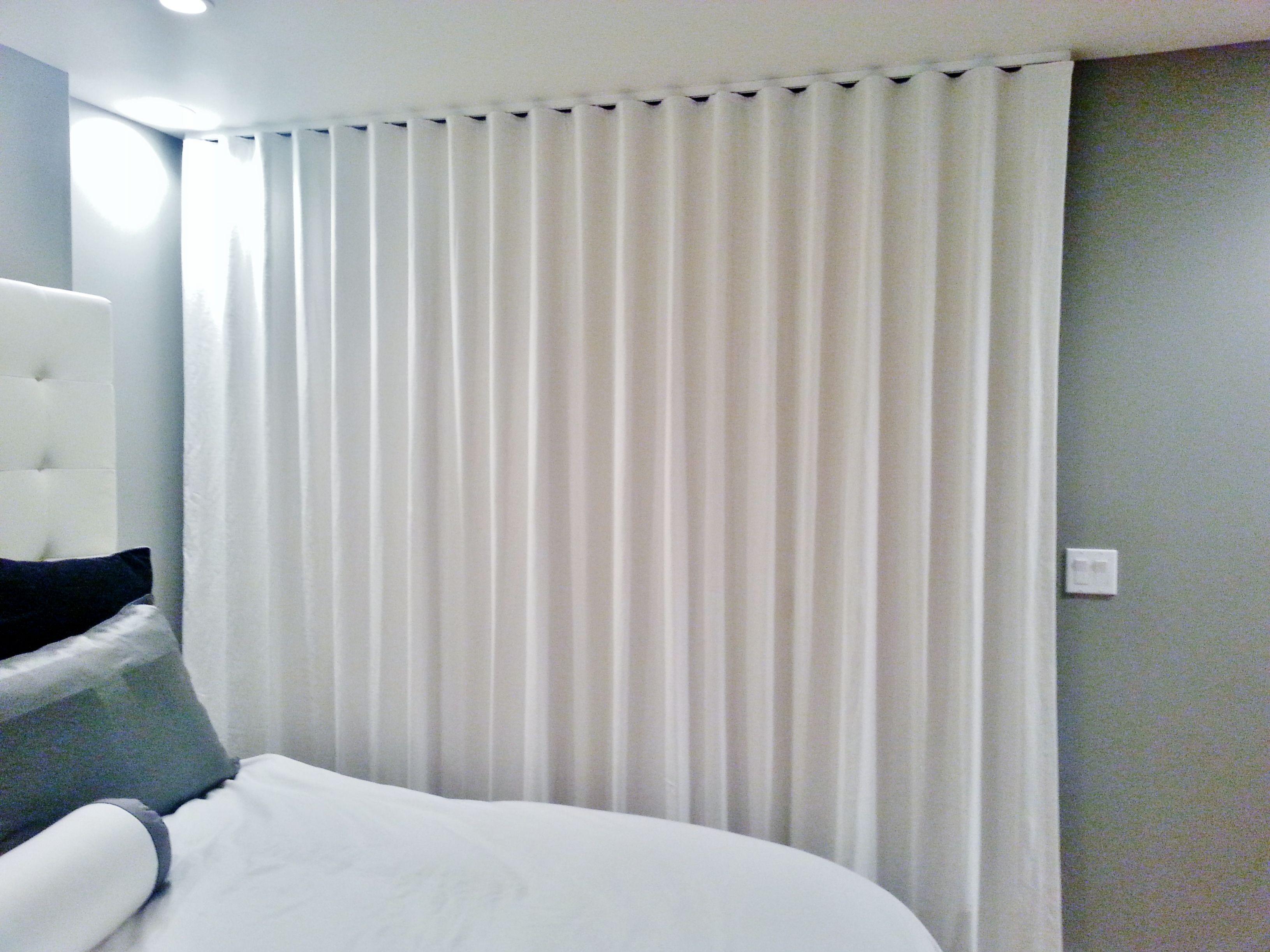 Ripplefold drapery panels on ceiling mounted architrac rod