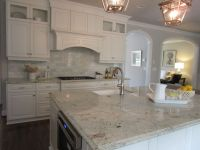 White kitchen, dark wood floors, marble backsplash ...
