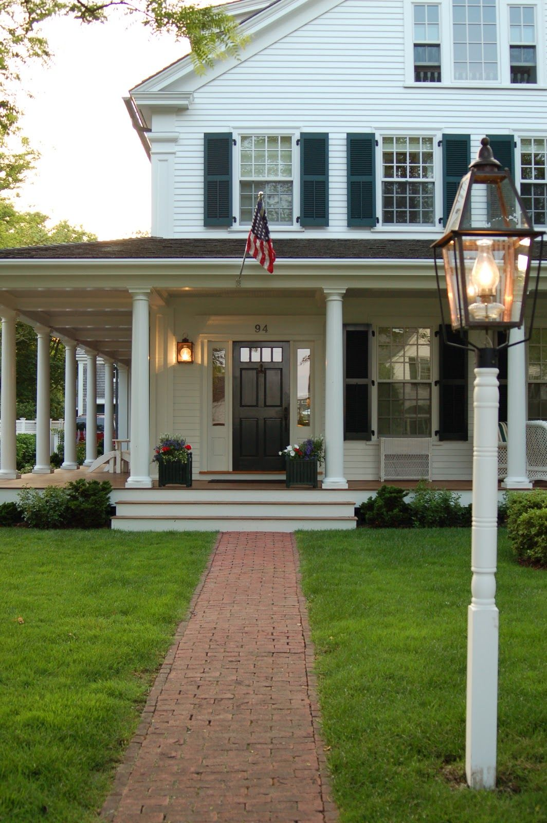 Traditional White House With Black Shutters And Big Front