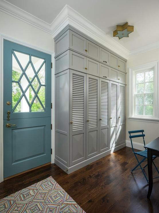 A turquoise blue door opens to a mudroom features builtin