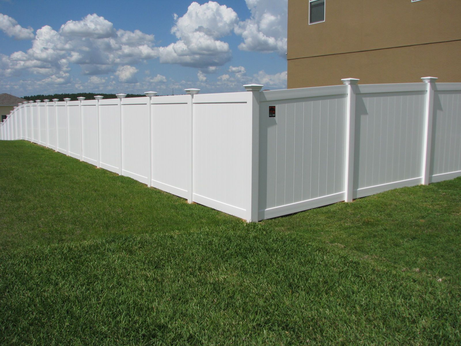 Backyard white vinyl privacy fence with caps  Mossy Oak