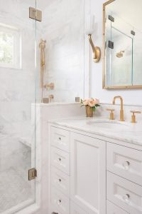 White and gold bathroom features a white washstand adorned ...