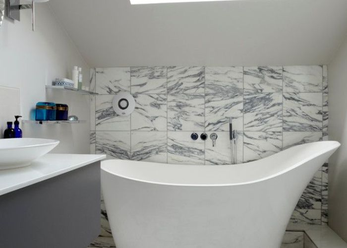 Classic bathroom with white curvy tub grey tiles wall and floor cabinet also