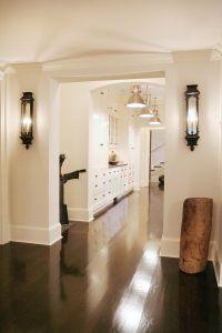 Hallway with dark wood floors, built-ins, wall lighting ...