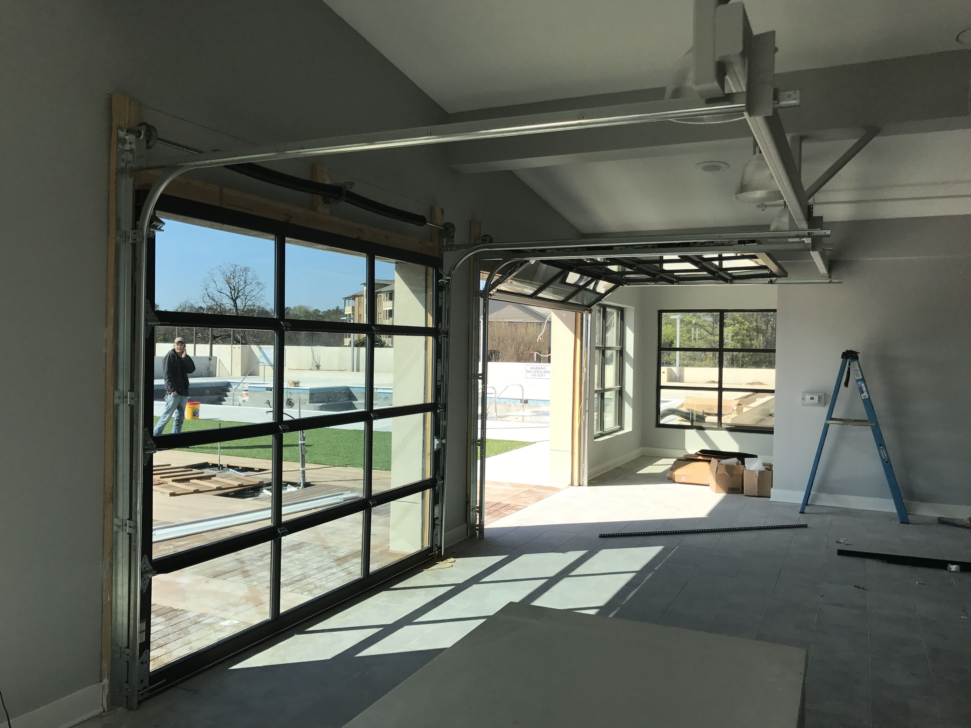Full view glass garage door separating game room from