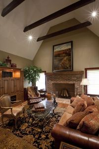 Brick fireplace with a wooden beam mantel, a cathedral ...