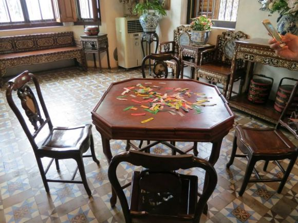 A table with checkee cards scattered across it. Along with mahjong, this was one of the most popular Peranakan games.