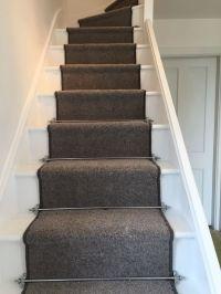 Grey carpet runner and chrome carpet rods on white painted