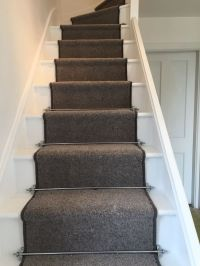Grey carpet runner and chrome carpet rods on white painted ...