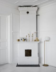 Vintage fireplace with brass decorations and mix of candle holders perfection in white dark hues by lotta agaton nordicdesign also rh pinterest