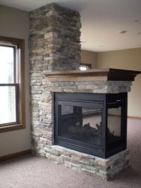 3 Sided stone fireplace with wood mantle in this LDK Lower ...