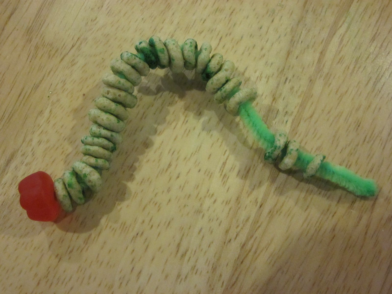 Caterpillar Snack Craft use a green pipe cleaner, red