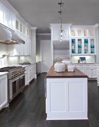 White cabinets, dark wood floors, wood countertop in ...