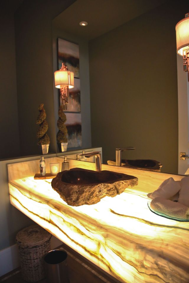 LED light shines through a white onyx countertop illuminating the