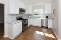 Beautiful warm wood floors, white cabinets, stainless ...