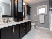Dark cabinets, white counter tops and a marble floor add ...