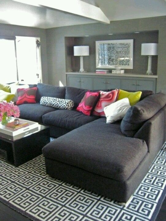 Simple Black Couch With Pops Of Color In The Pillows And Flowers