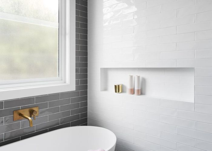 Gray subway tiling in  serene pink  white bathroom also bathtubs
