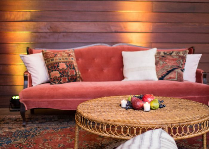corporate party dark pink velvet sofa with turkish kilim throw pillows and  mid century wicker coffee table over an antique blue red persian rug also the vaughn france photographers