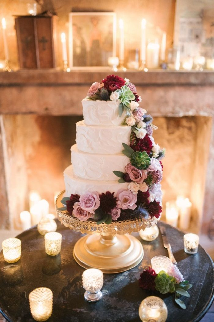 four tier white wedding cake with mauve and dark red