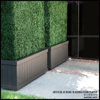 Tall artificial hedges in dark brown planters create a ...
