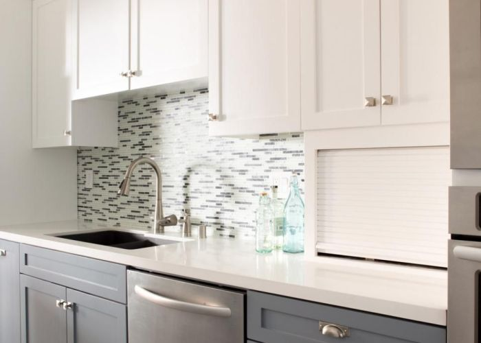 Light plays off the glass tile backsplash and stainless steel dishwasher adds  sleek touch to this midcentury modern kitchen white upper cabinets also