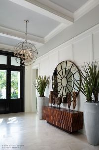 Entryway with black front door, large round mirror, orb ...
