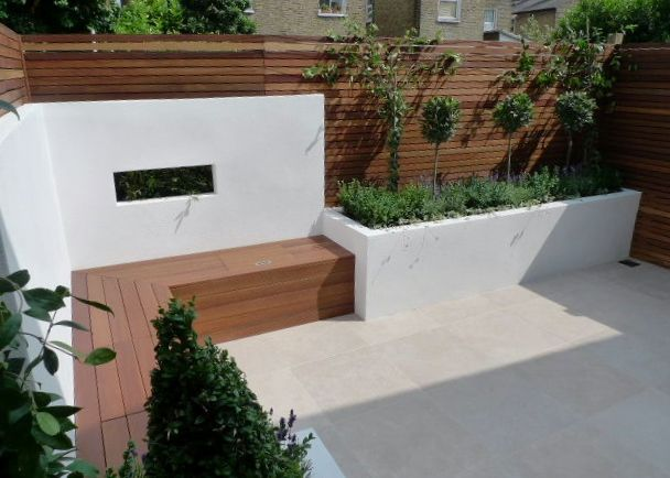 Contemporary Garden Decking Area With Low Rendered White Walls