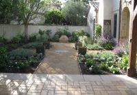 Formal Mediterranean garden with small stone fountain ...