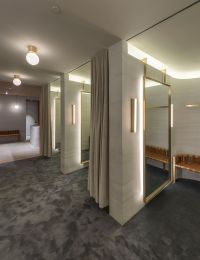 Striated concrete partitions create fitting rooms at ...