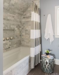 A gorgeous bathroom remodel with a tile shower, white trim ...