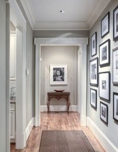 Hallway gallery white thick moulding light gray black frames and mats wood floors also neural walls trim accents please rh pinterest