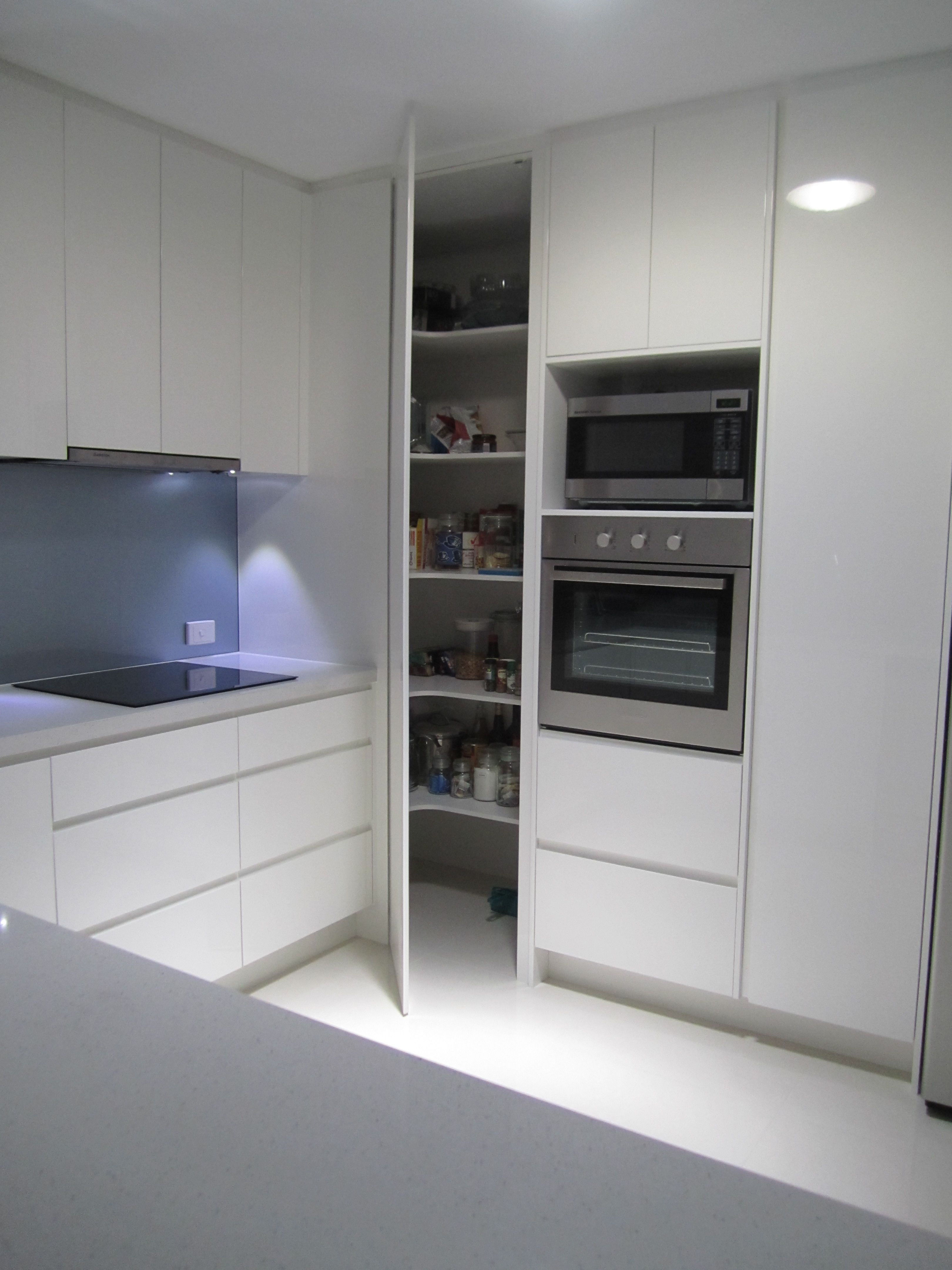 Two Ovens In Vertical Alignment With Pantry Door Alongside