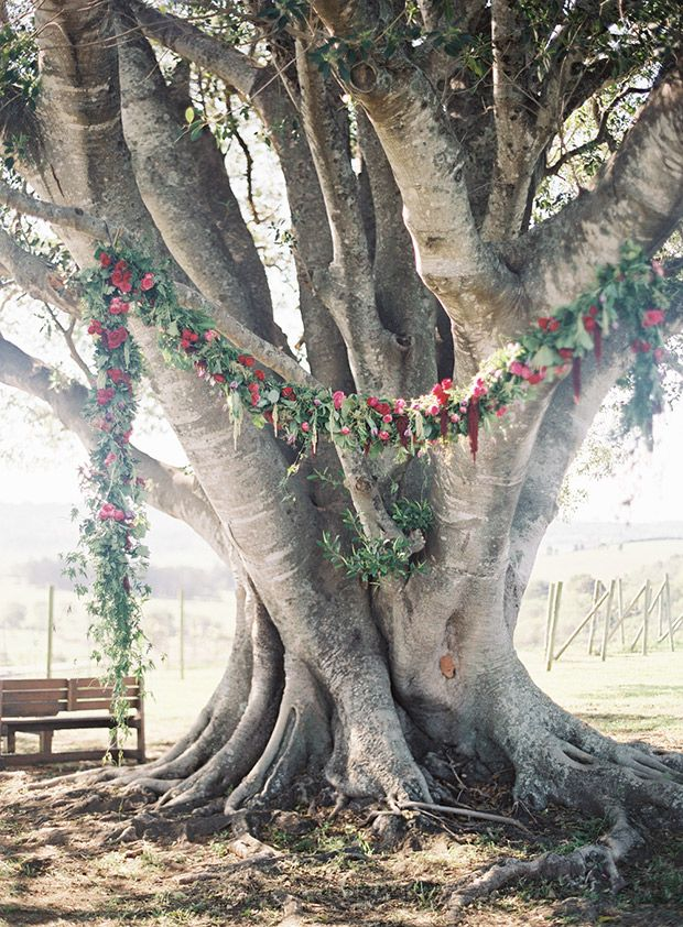 Under a wedding tree outdoor wedding ceremony location under a beautiful red floral garland