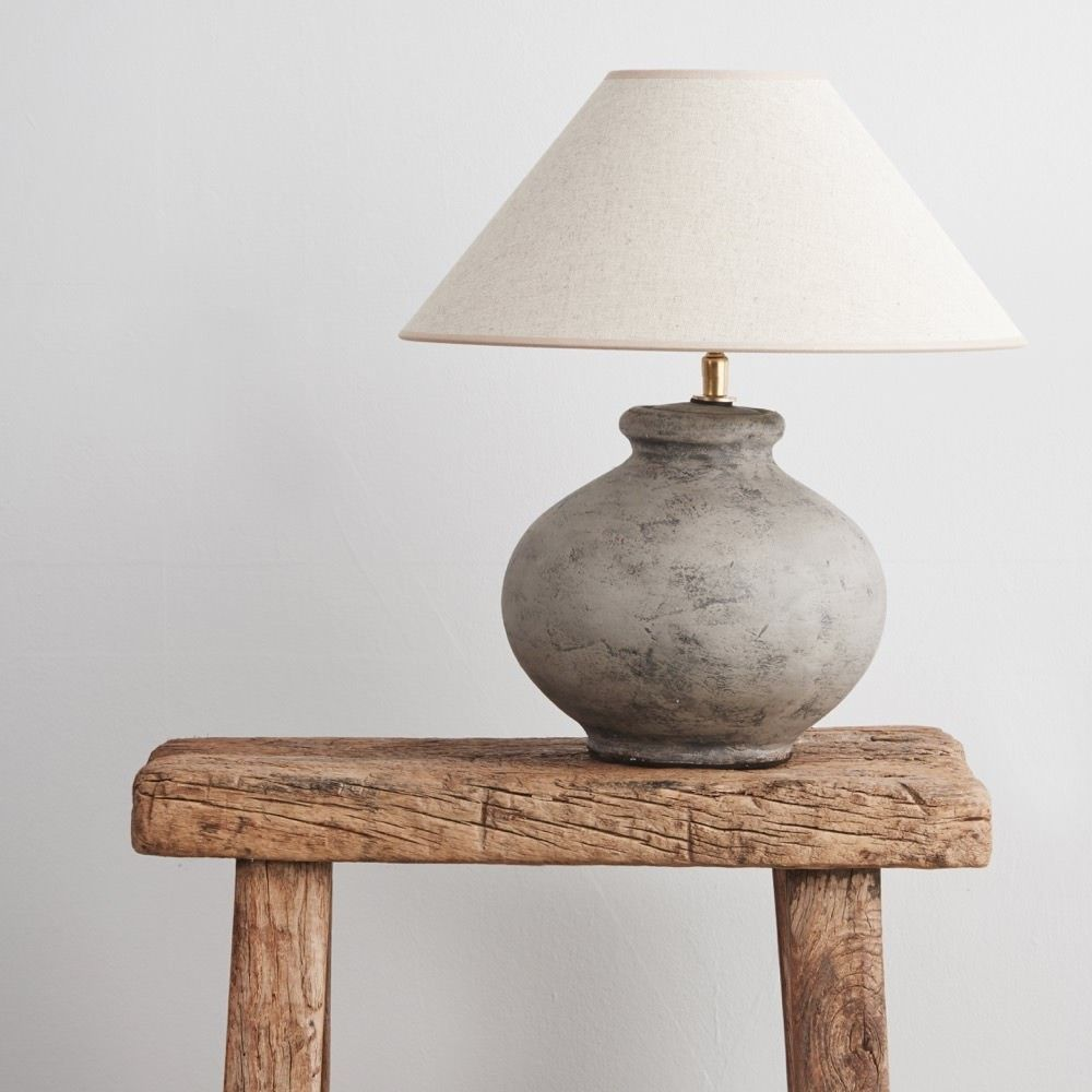 This table lamp features an unfinished ceramic base with