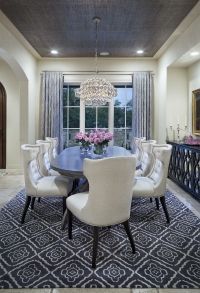 cream-colored dining room with grey rug, curtains and ...