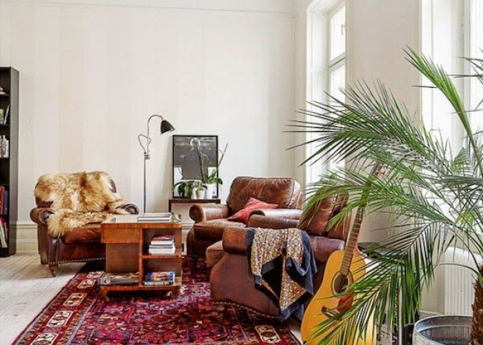 Comfortable vintage leather chairs and  lovely persian rug also millennials investing in rugs for the home