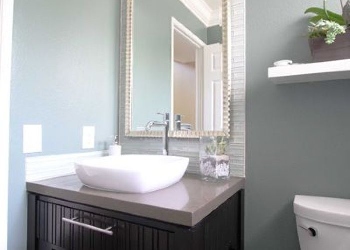 In this soothing blue gray and white contemporary bathroom small details add visual texture such as the framed mirror glass tile backsplash also guest downstair to