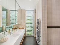 Privacy louvre windows adds light to a narrow bathroom. #