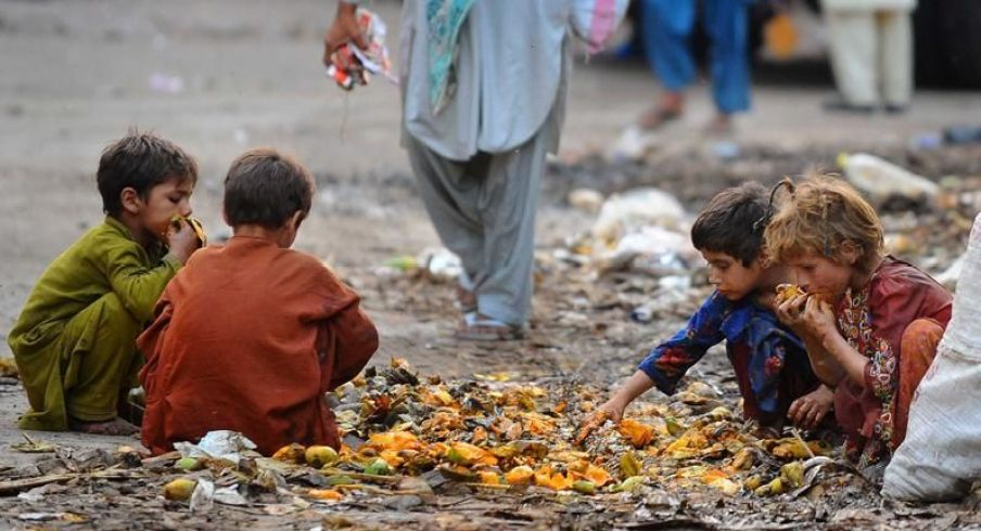 4 children eating squashed fruit off of the filthy ground - Surrounded by trash.