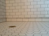 white subway tile shower with marble pencil trim detail in ...