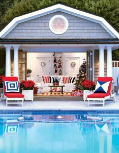This nautical pool house in tiburon california gets  holiday makeover with sailboat themed christmas tree hand knitted stockings and fresh red also hate the roofline love little covered porch idea rh pinterest