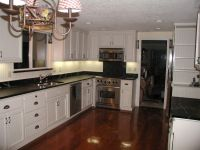 kitchens with white cabinets and black countertops ...