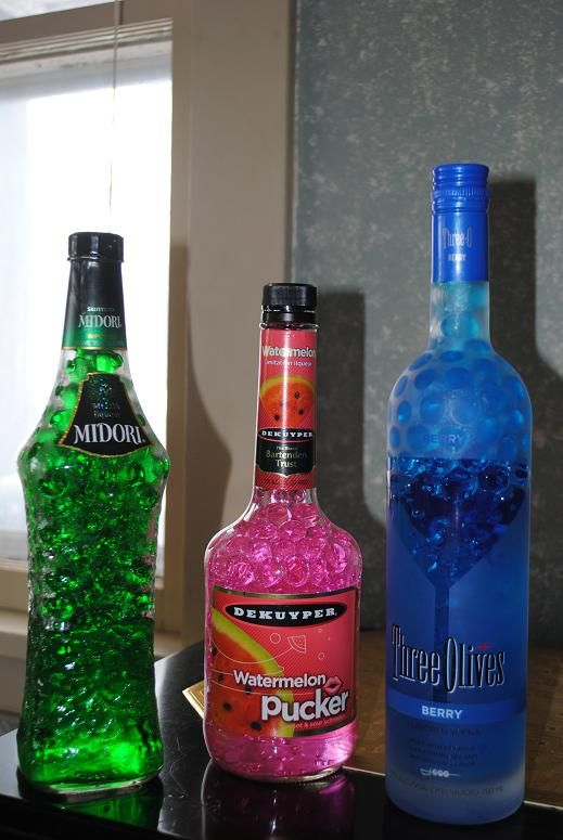 Fill empty alcohol bottles with bright colored water beads