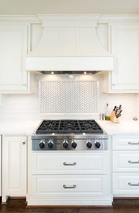 A white paneled French kitchen hood stands over a white
