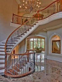 Elegant two-story marble foyer with floating staircase ...