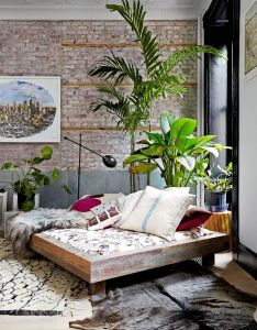 Brick wall exposed in living room with rich color palette and tall indoor plants also tour  tribeca loft charming details bricks walls rh pinterest