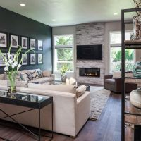 The dark accent wall, fireplace and custom wood floors add ...